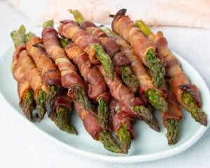 "A recipe for keto bacon wrapped asparagus that can be served as a side dish, and adding a Swerve Brown ""sugar"" glaze makes these over-the-top delicious."