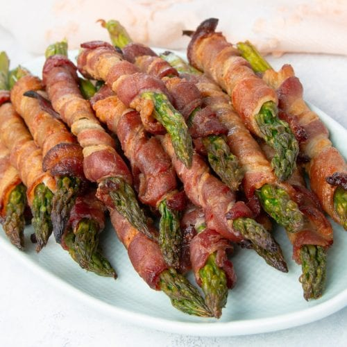 """A recipe for keto bacon wrapped asparagus that can be served as a side dish, and adding a Swerve Brown """"sugar"""" glaze makes these over-the-top delicious."""