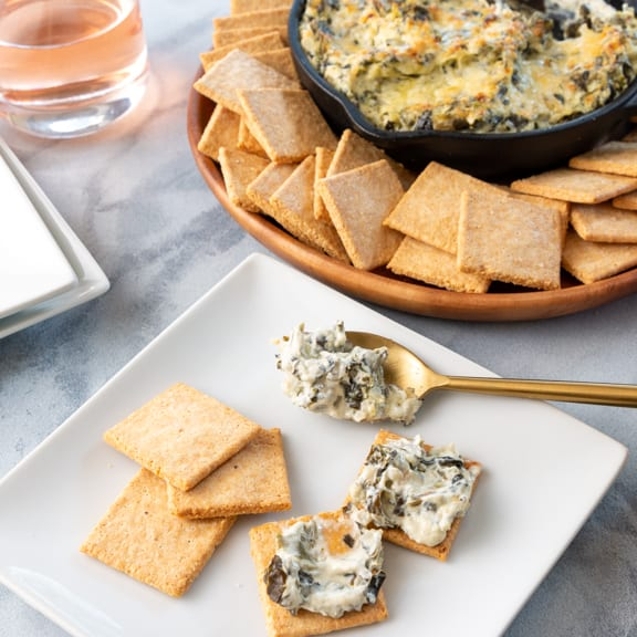 keto cheddar crackers with spinach artichoke dip spread on them.